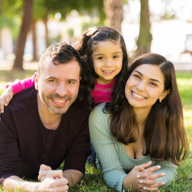 A smiling family composed by father, mother and a young girl lying on grass.