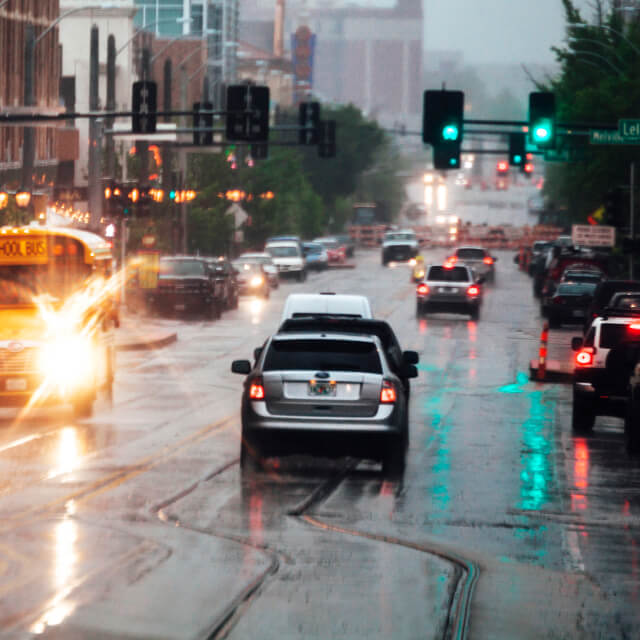 Photo of a busy street with cars and buses driving under the rain.