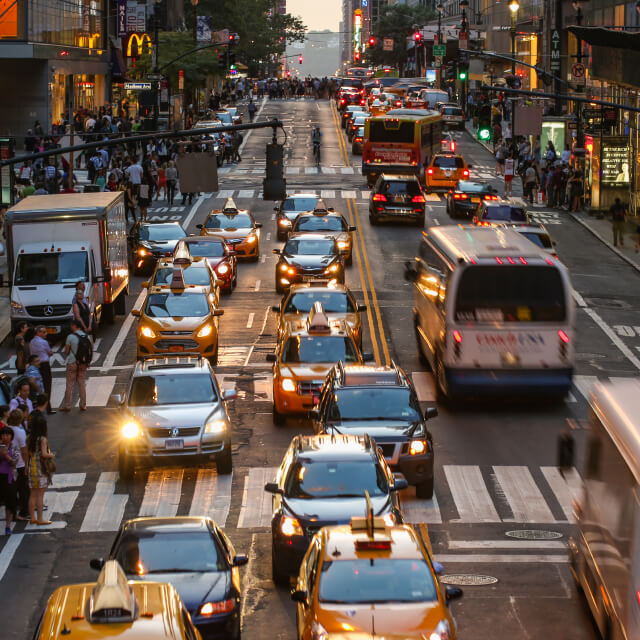 Photo of traffic on a street in New York City with cars, taxis and buses going in both directions.