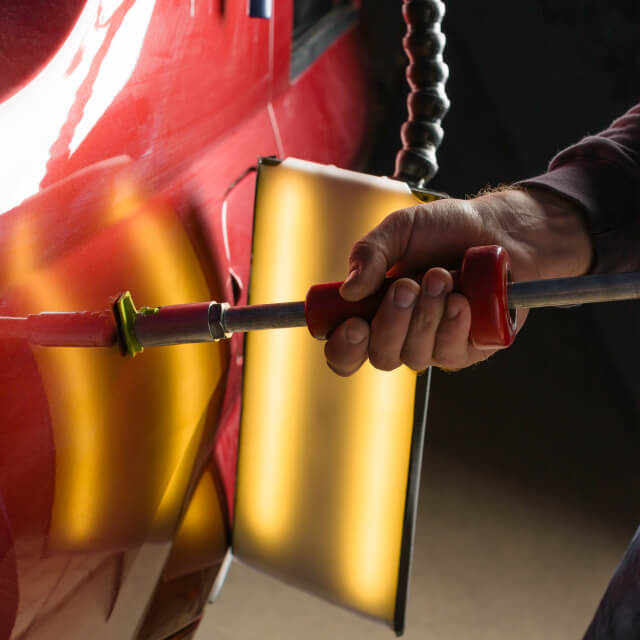 Illustrative image of a person repairing a car dent using a tool.