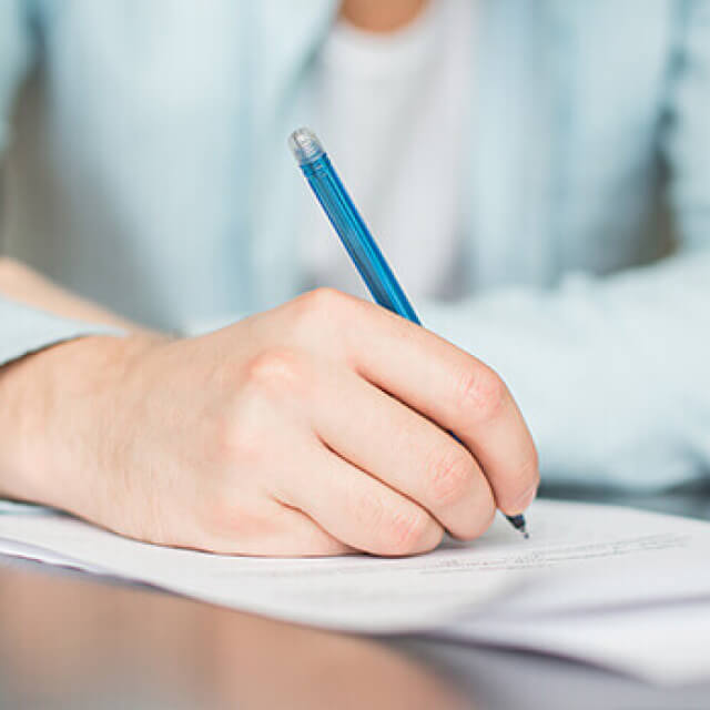 A person writes or signs on a piece of paper using a blue pen.