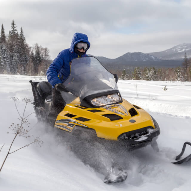 A man riding a snowmobile with a forest and mountains in the background.