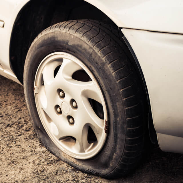Image of the damaged flat tire of a white car with rim.