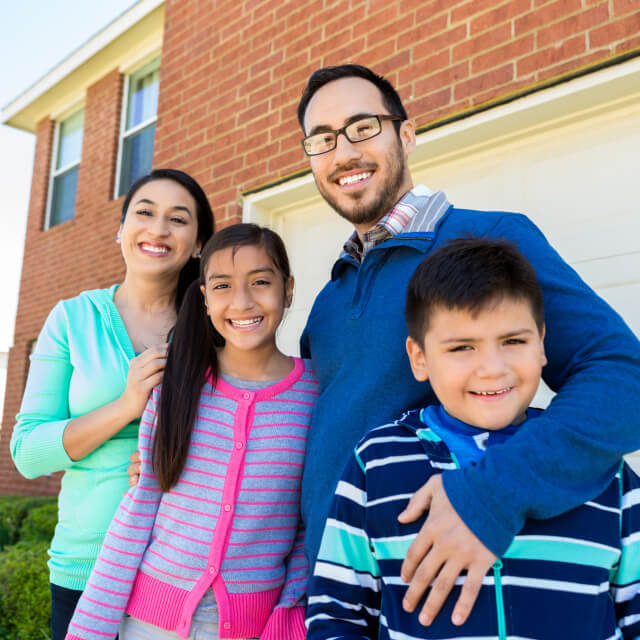 A family composed by a man, a woman, a boy and a girl smiling in front of a house.