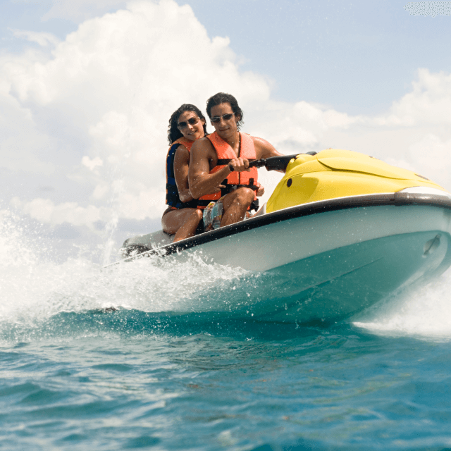 A man and a woman wearing safety vests ride a jet ski.