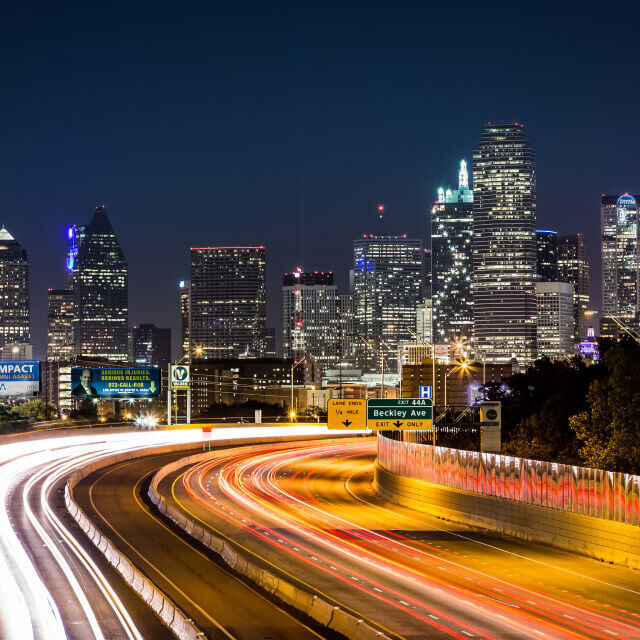 Picture of Dallas city at night including a main road with high buildings in background.
