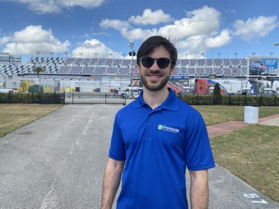 NASCAR Driver Daniel Suarez wearing Freeway Insurance shirt standing outside of race track stadium