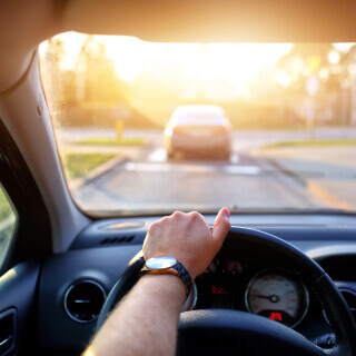 Front view of driver in car with cheap car insurance driving in highway during sunset
