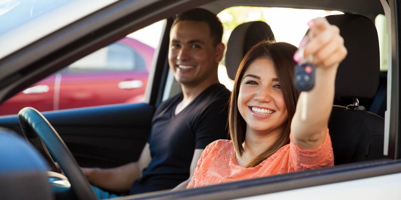Smiling woman in a cars drivers seat holding keys up with a man as passenger