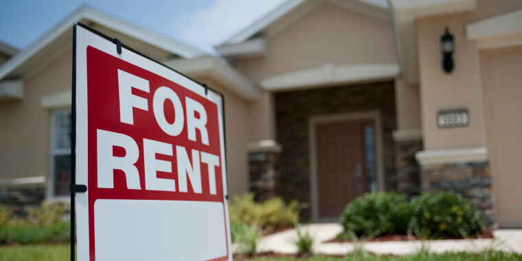 Close up of a sign that says for rent with a house on the background