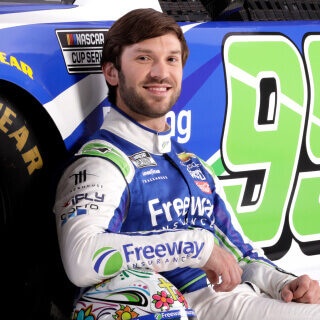 Front view of NASCAR Cup Series Driver and Xfinity Series Champion Daniel Suarez posing with Freeway Sponsored Chevrolet race car