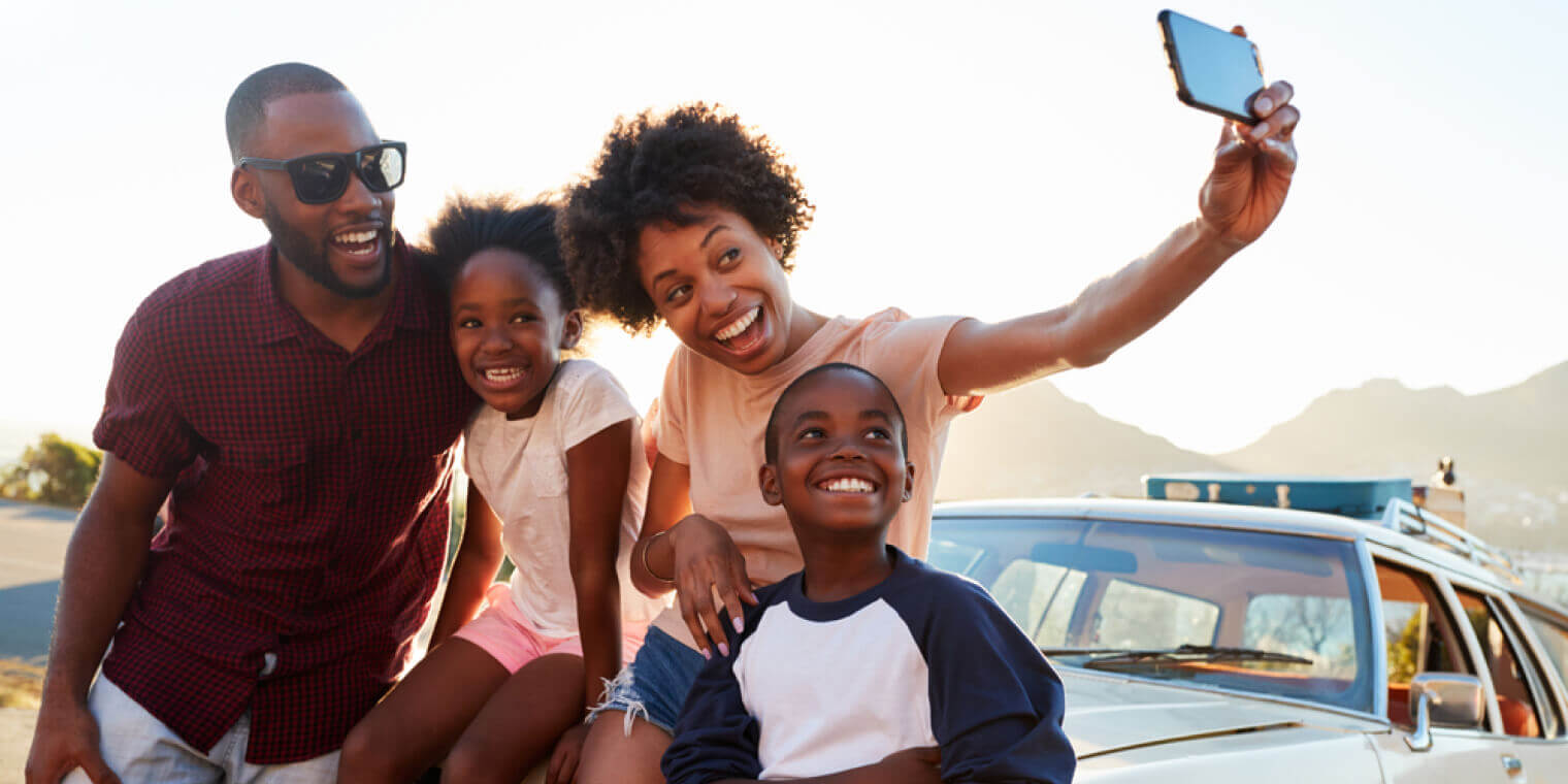 African American family posing for selfie next to car packed for road trip with car insurance