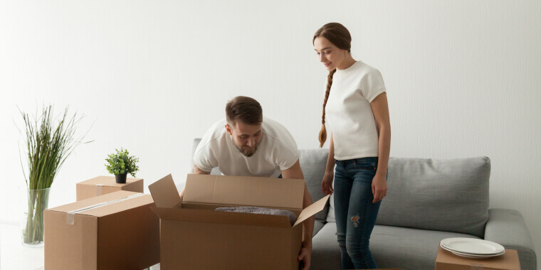 Couple in rented apartment moving boxes