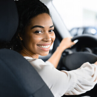 African american woman smiling and looking at the camera sitting in a cars drivers seat