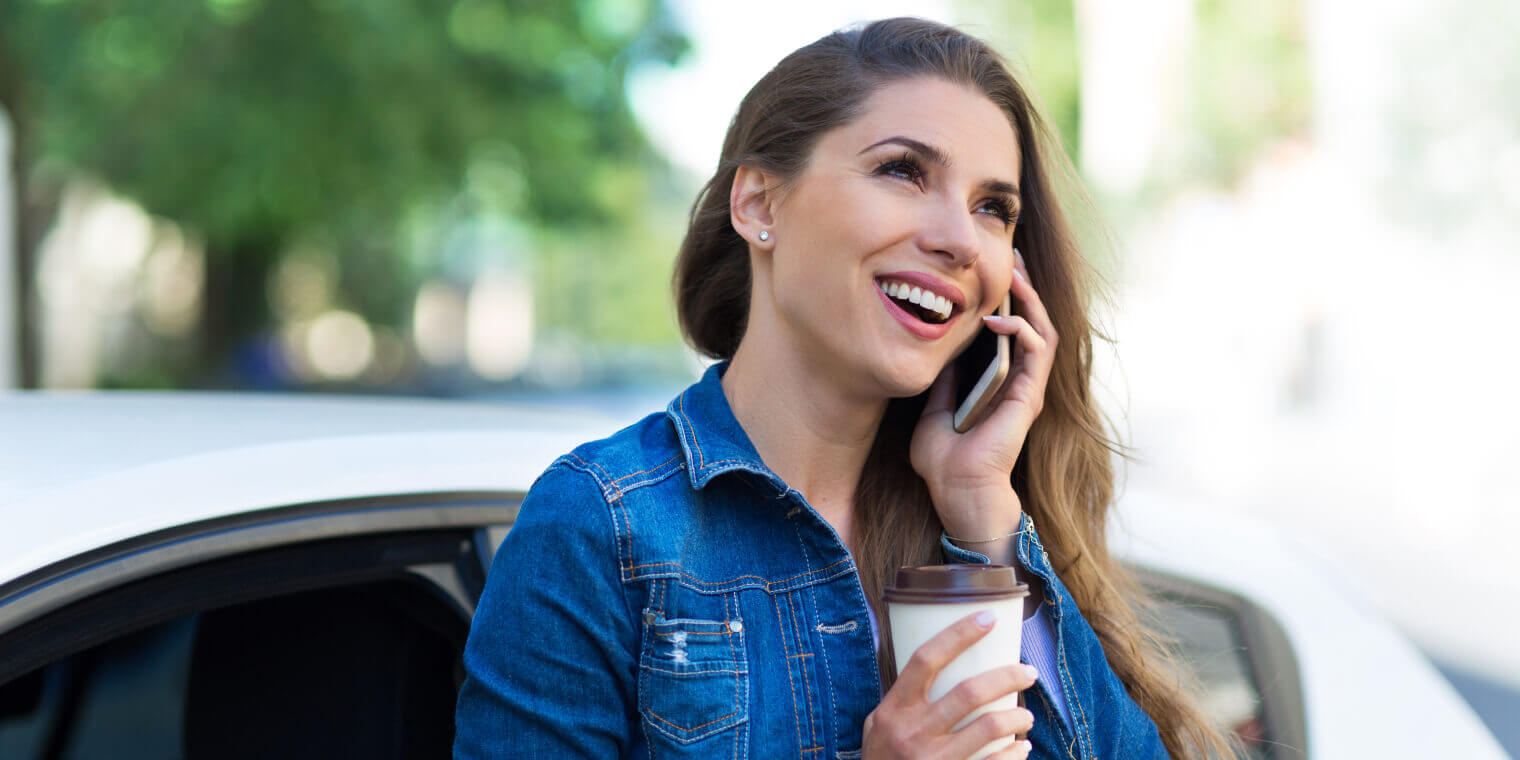 smiling woman holing a coffee leaning on a car talking on smartphone
