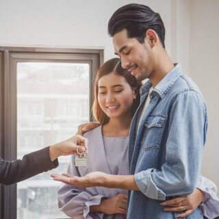 Young happy couple getting house keys.