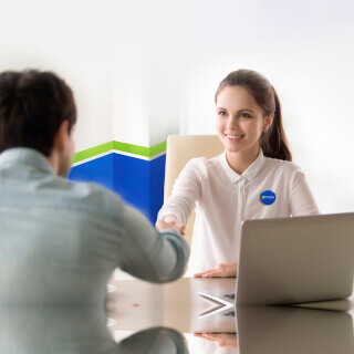 Female agent and customer shaking hands at Freeway Insurance office.