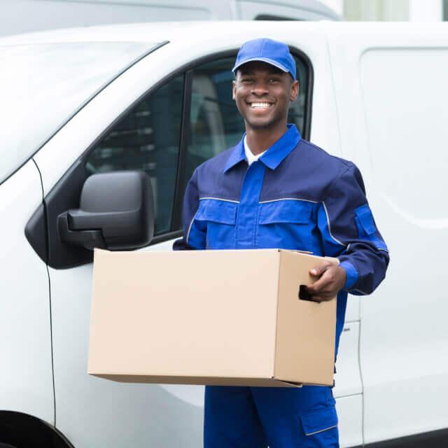 Deliveryman smiling outside a car holding a carton box.