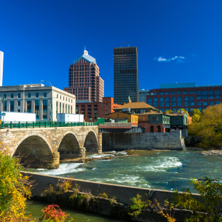 Downtown Rochester skyline in the background with a stone bridge, the Genesee River, and plants in the foreground.